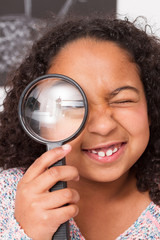 Mixed child playing to explore with magnifying glass