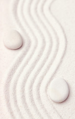 Zen garden with a wave lines in the sand with relaxing white sto