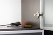 Leinwanddruck Bild - An adjustable concealed hinge fixed on a modern cabinet with a glass door, and two screwdrivers