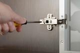 A man uses a screwdriver to adjust a concealed hinge fixed on a modern cabinet with a glass door