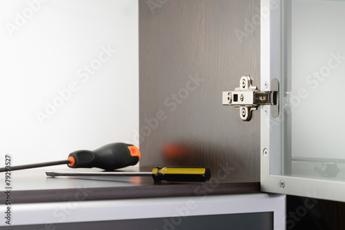 Leinwanddruck Bild An adjustable concealed hinge fixed on a modern cabinet with a glass door, and two screwdrivers
