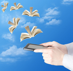 Hand with electronic book and opened books flying