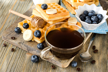 Fresh waffles with cup of coffee and blueberries for breakfast