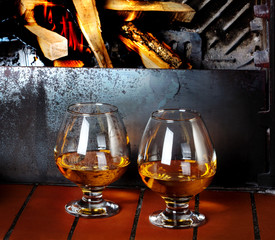 Two tanks of cognac on the old brick fireplace with a bright fir