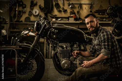 Mechanic building vintage style cafe-racer motorcycle  - 79298700