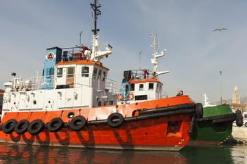 Tug boat against dramatic blue sky