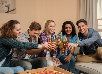 Friends with pizza and bottles of drink celebrating