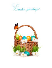 Happy Easter background. Basket with eggs, daisies, grass and a