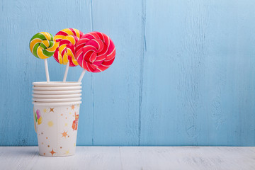 cups and lollipop on the blue wooden background