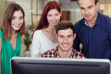 vier junge leute schauen auf computer-bildschirm