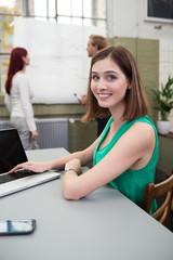 junge frau arbeitet am laptop mit kollegen im hintergrund