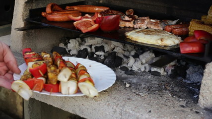 Barbecue grill with kebab meat, sausages, vegetable and cheese.