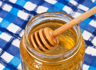 Breakfast honey on blue white tablecloth, with wooden dipper.