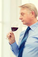 older man smelling red wine