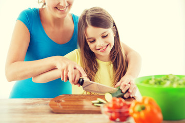 smiling little girl with mother chopping cucumber