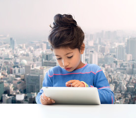 little girl with tablet pc over city background
