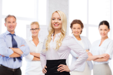 smiling businesswoman over office team
