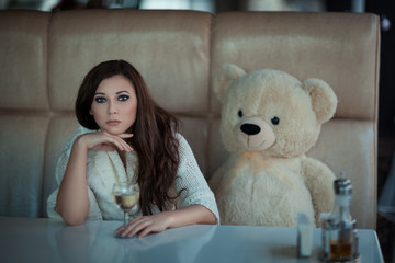 Sad girl at the table with a toy bear.