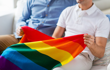 close up of male gay couple holding rainbow flag