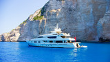 Luxury white yacht navigates into beautiful blue water near Zaky