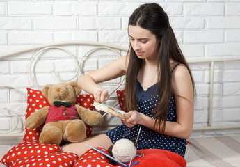 pretty girl seamstress engaged in embroidery on the bed