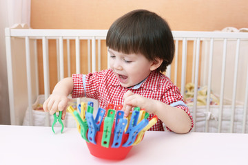 toddler plays with clothes pins