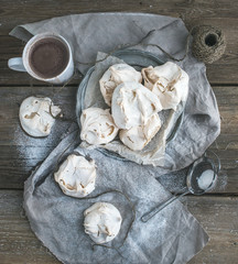White meringue and mug of hot chocolate on a rustic wooden table
