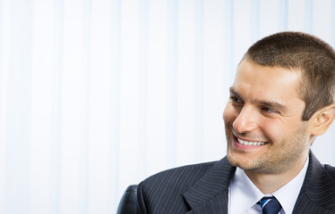 Happy smiling young businessman, at office