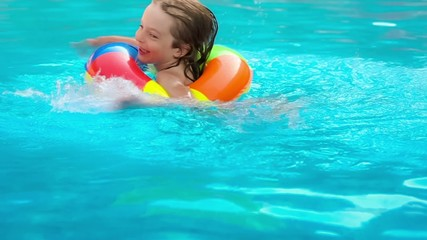 Happy child having fun in swimming pool. Slow motion