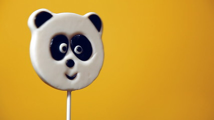 lollipop in the form of an panda on a yellow background