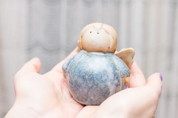 Hands holding angel figurine