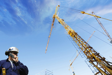 building worker and construction site, cranes and scaffolding