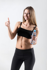 Sporty girl with bottle of water showing thumbs up