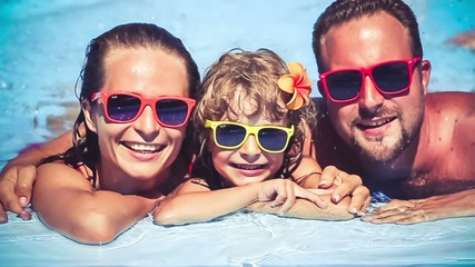 Happy family having fun in swimming pool. Slow motion