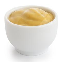 Smooth mustard in white ceramic ramekin. White background.
