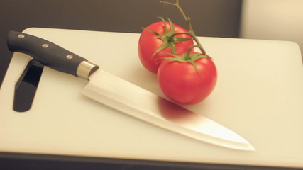 fresh tomatoes and knife at the table