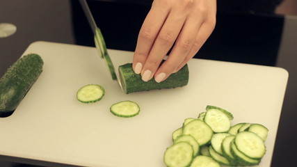 woman cuts cucumber at the kitchen