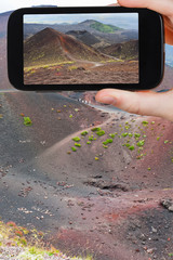 tourist taking photo of path on slope of craters