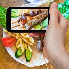 tourist taking photo of skewers mix arabic kebabs