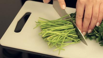 woman cuts fresh parsley