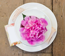 table setting with blooming pink peony. Shallow depth of field