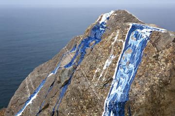Roca pintada de azul y blanco sobre el mar