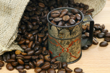 measuring cup  and a burlap bag with coffee beans background