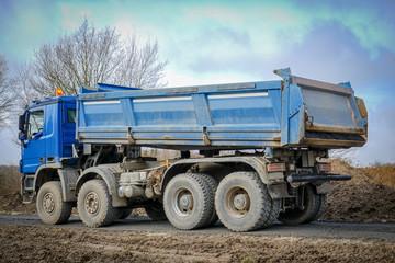 Straßenbau, blauer  Lkw will Schotter abkippen