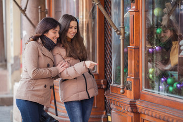 Two happy young women window shopping in the city