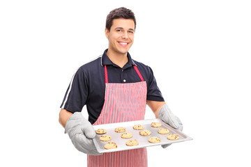 Man holding a pan full of chocolate chip cookies