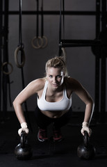 Doing push up with kettlebells