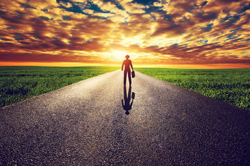 Man with suitcase and hat on long straight road to sunset sun