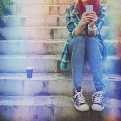 Hipster teenage girl with smartphone and takeaway coffee