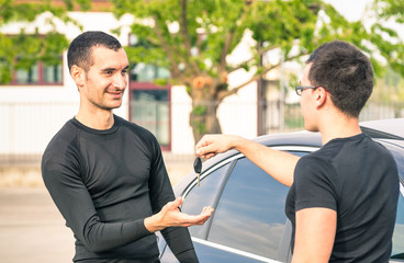 Happy young man receiving car keys after second hand sale